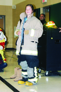 Caledon Fire and Emergency Services chose SouthFields Village Public School as the place to kick off Fire Prevention Week Monday. Fire Chief Dave Forfar urged the student to ask their parents for smoke alarms in their bedrooms. The celebrations included students trying on firefighting gear. Brooklyn Stephenson was posing with her outfit, while Firefighter Jesse Newcombe was assisting Tyrell Campbell. Photos by Bill Rea