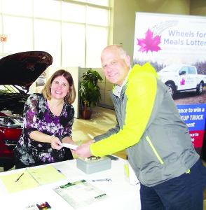 Jan Holland, father of Arizona Coyotes skater (and former Toronto Maple Leaf) Peter Holland, purchased the first lottery ticket from Christine Sevigny, executive director of Caledon Meals on Wheels. Photos by Mark Pavilons