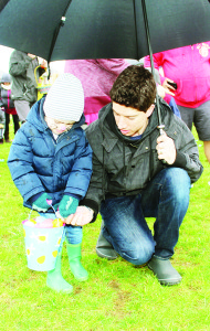 The rain was no problem if there was an umbrella handy. Loretto Veneziale, 3, was able to concentrate on collecting his eggs while his father Steve helped keep him dry.